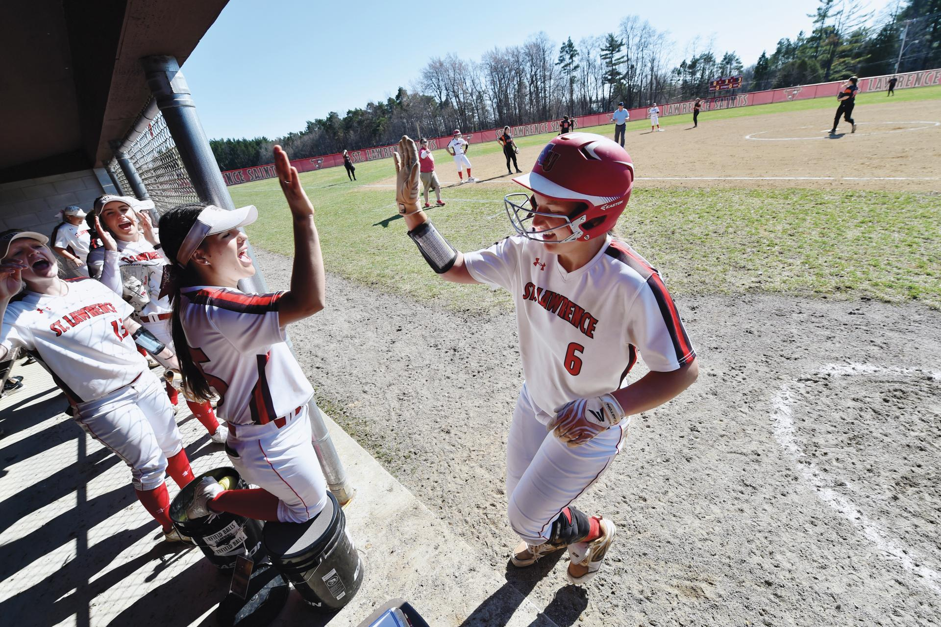 Elle Gray '19 high-fiving a teammate in the dugout during a game