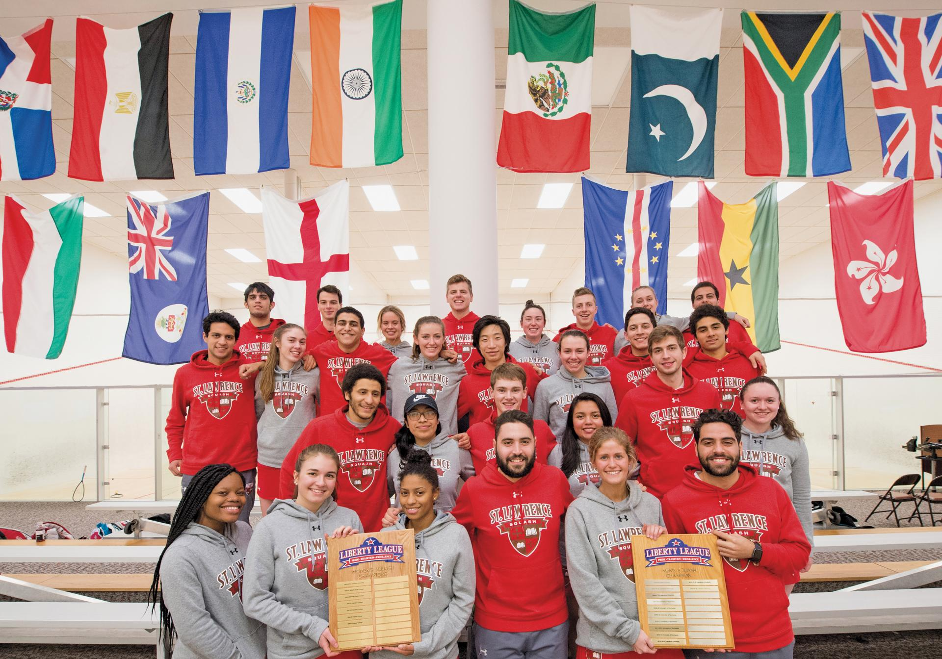The Saints' men's and women's squash teams showing off their Liberty League Championships titles from this season.