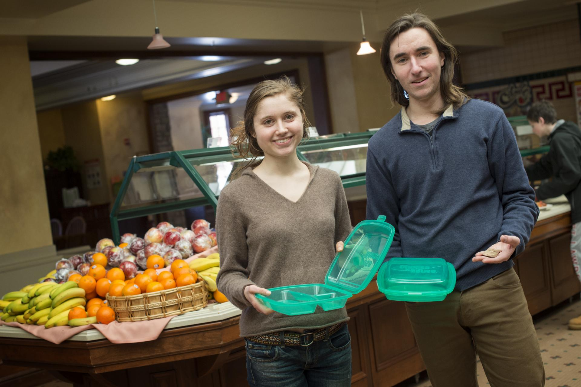 Lanika Sanders '16, left, and Kealey Viglielmo '16 display the to-go containers that have reduced the University's contribution to the waste stream.