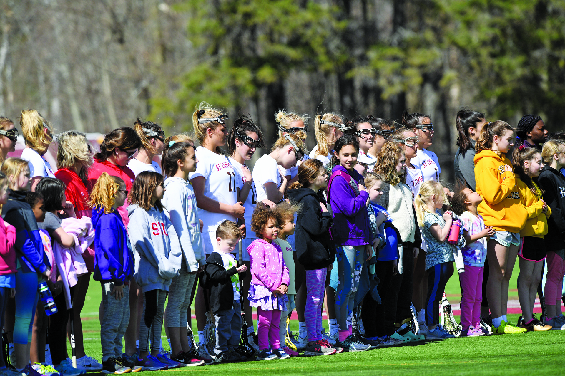 Local girls and boys join the Saints women's lacrosse team on the field prior to its 16-6 victory over Bard College on April 13.