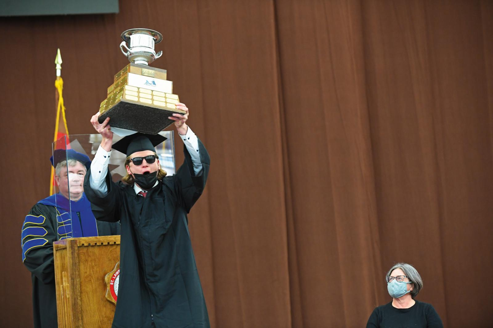 Hockey player lifting ECAC Men's Hockey Trophy at Commencement
