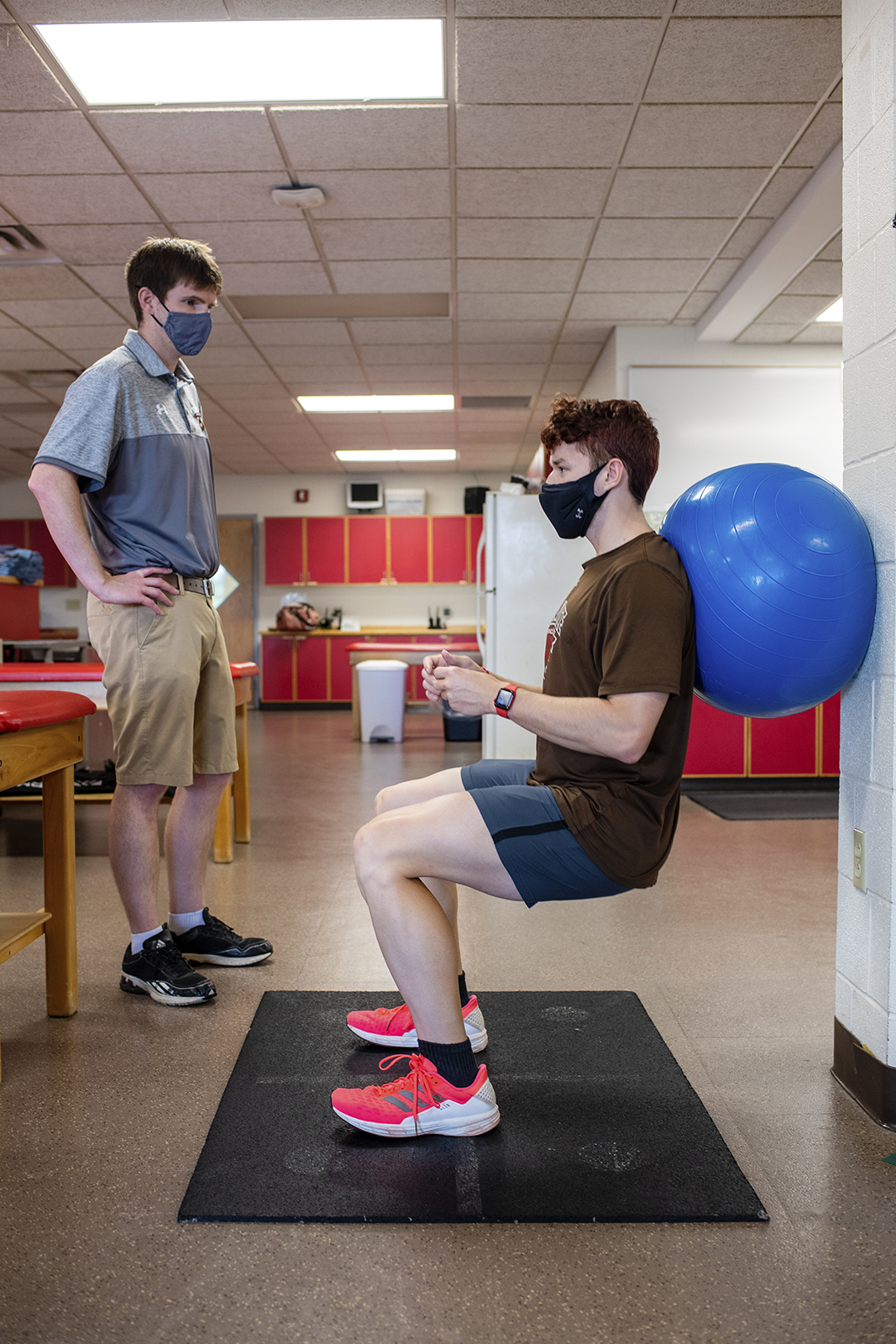 An athlete does wall sits against a blue workout ball while a trainer watches over them
