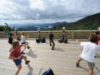 Students participating in Tai Chi on the deck of an overlook.