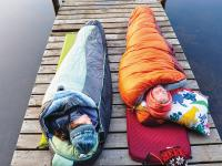 Two students sleeping in sleeping bags on the dock